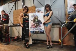 大会スポンサーであるゲーム「アーキエイジ」のポスターをもつディーバの美しいお二人。