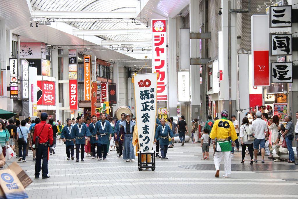 市内商店街を先導して進む神幸行列。(昨年)