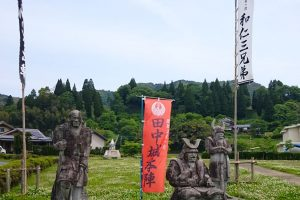 田中城跡に建つ和仁3兄弟の石像。左奥が人鬼、和仁親宗。