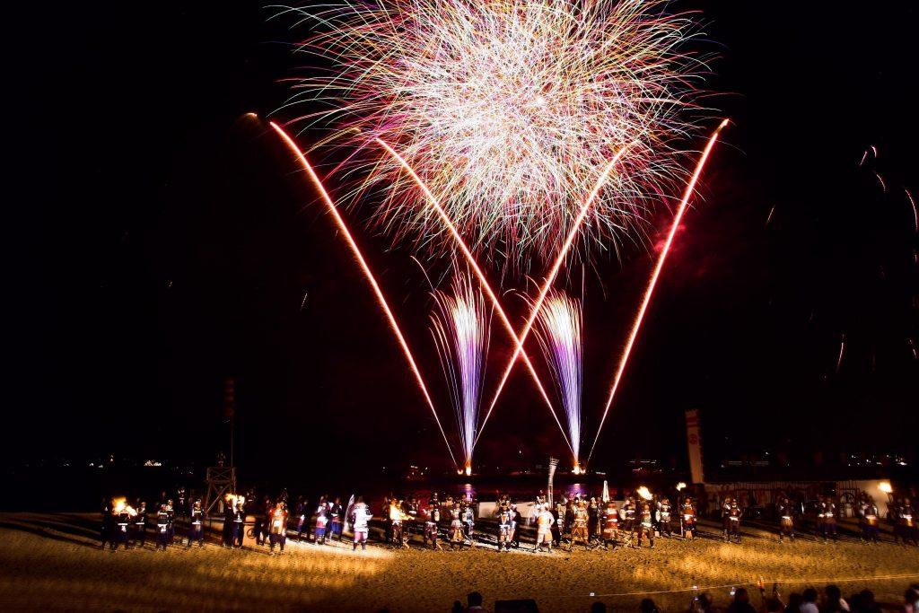 浜辺に並ぶ武者たちの後ろで大きくあがる大花火。